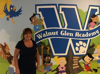 Mrs. Alexander standing in front of our Walnut Glen mural