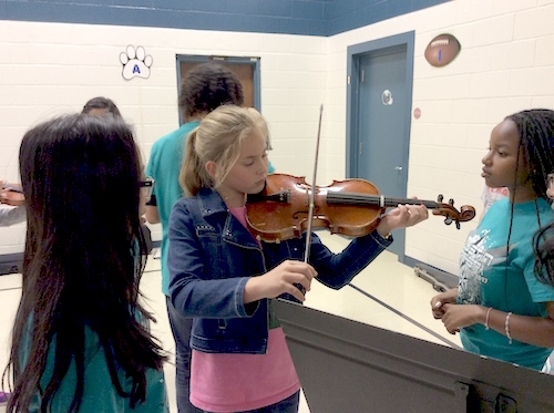 2 female students are watching another play the the violin.