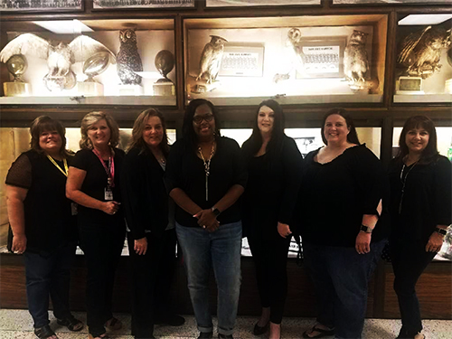 Counselors in front of display case with owls